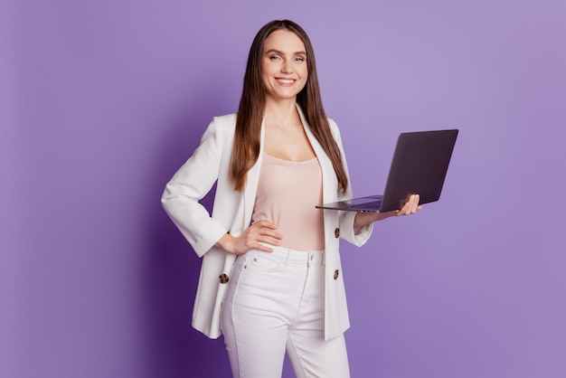 Close up portrait of charming business lady hold computer remote job concept on violet wall