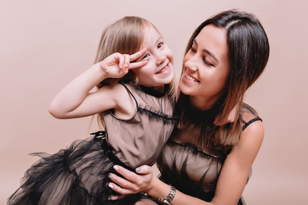 Close-up portrait of charming cute girl and her stylish mother wearing similar black dresses on beige wall