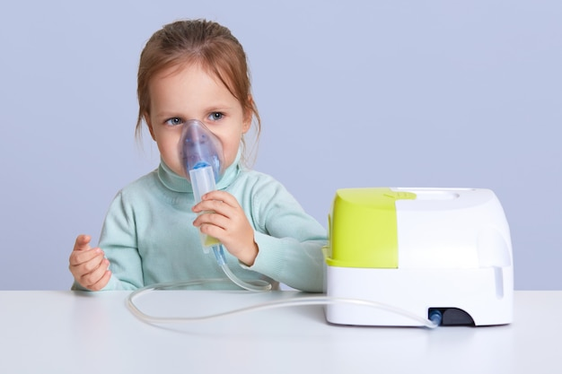 Close up portrait of charming cute small girl uses nebulizer mask for inahlation, has respiratory disease, sits at white desktop, isolated over white wall. little girl cures cough or pneumonia
