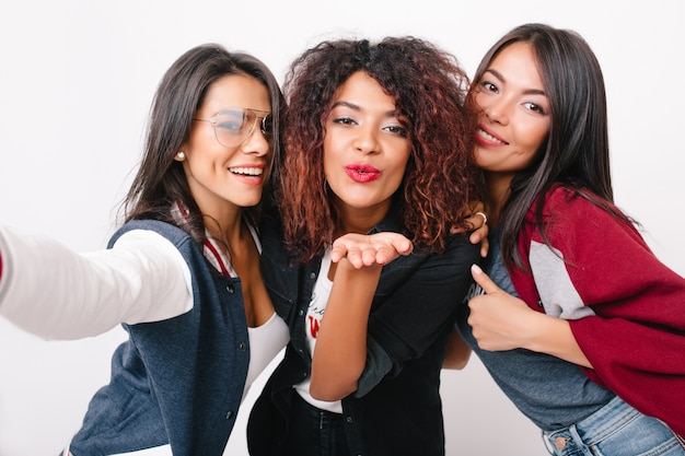 Close-up portrait of charming multiracial girls posing. elegant african young woman with red lipstick sending air kiss while her friends laughing.