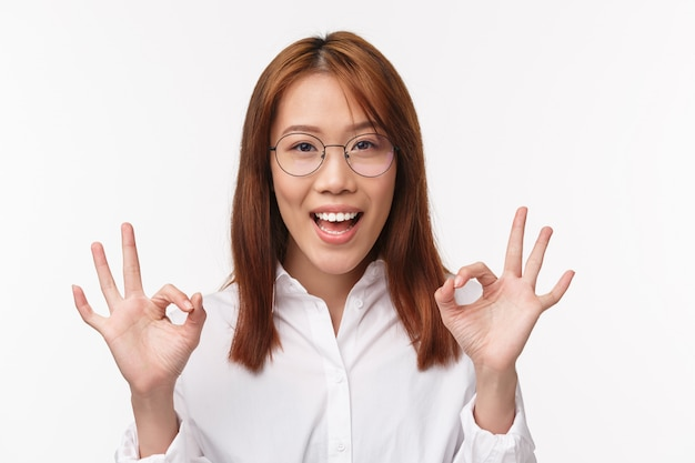 Close-up portrait of cheerful asian woman showing okay, good gesture, satisfied with great choice, guarantee quality and perfect service, assure all excellent, standing pleased