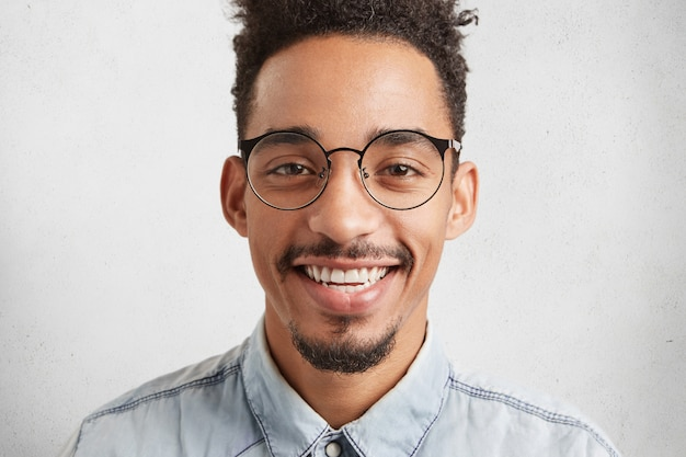 Close up ritratto di allegro maschio dalla pelle scura con baffi e barba,