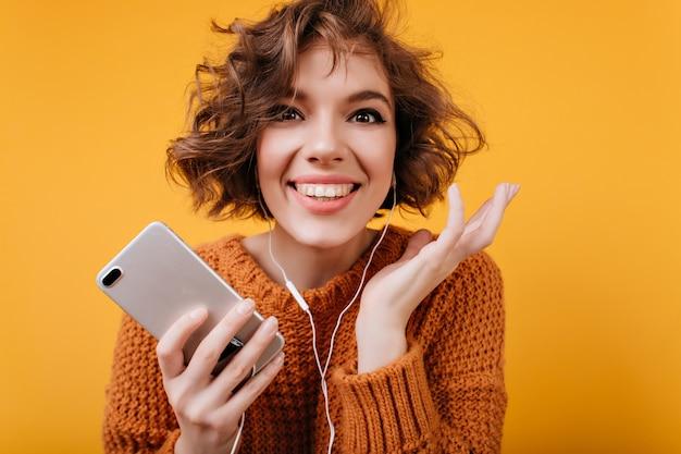 Ritratto del primo piano del modello femminile allegro che gode della musica preferita durante il servizio fotografico