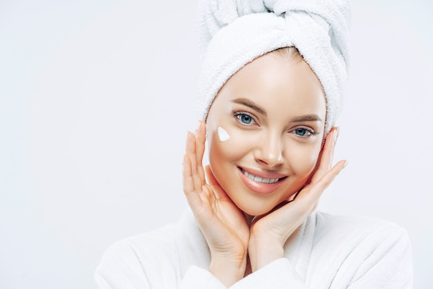 Close up portrait of cheerful female with natural beauty, touches cheeks gently, applies face cream for soft skin, wears bath towel on head, dressed in robe, stands indoor. beauty treatment, lifestyle