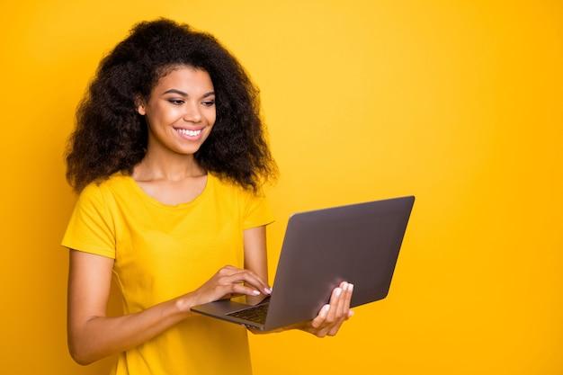 Макро портрет веселая девушка держит в руках ноутбук, создавая проект