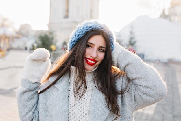Ritratto del primo piano della ragazza allegra con capelli neri lunghi che posano nella mattina di inverno sulla città della sfuocatura. signora castana in berretto blu che gode del servizio fotografico in una giornata fredda.