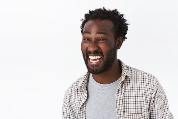 Портрет крупным планом, веселый красивый беззаботный бородатый афро-американский парень, смеющийся и возбужденный искоса