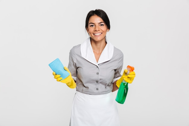 Close-up portrait of cheerful maid in uniform holding rag and cleaning spray