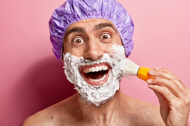 Close up portrait of cheerful man has morning routine, applies shaving gel on face, smiles broadly, being in good mood