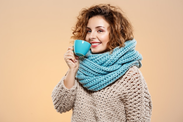 Close up portrait of cheerful smiling beautiful brunette curly girl in knitted sweater and grey neckwarmer holding cup over beige wall