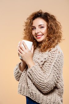 Close up portrait of cheerful smiling beautiful brunette curly girl in knitted sweater holding cup over beige wall