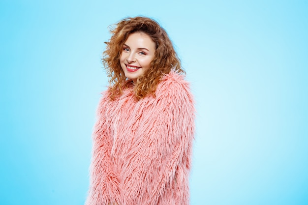 Close up portrait of cheerful smiling beautiful brunette curly girl in pink fur coat over blue wall