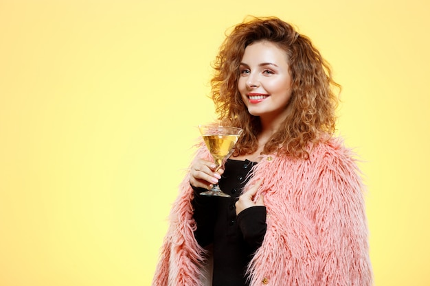 Close up portrait of cheerful smiling beautiful brunette curly girl in pink fur coat holding cocktail glass over yellow wall