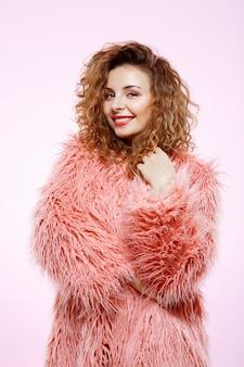 Chiuda sul ritratto di bella ragazza riccia castana sorridente allegra in pelliccia rosa sopra la parete bianca