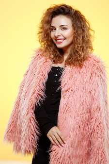 Close up portrait of cheerful smiling beautiful brunette curly girl in pink fur coat over yellow wall