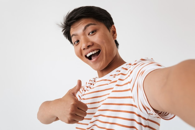 Close up portrait of a cheerful young asian man showing