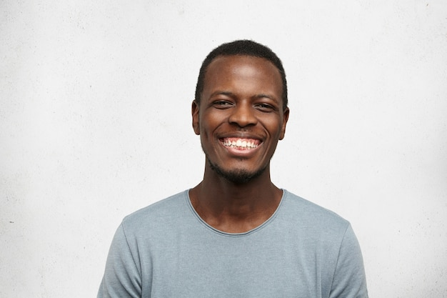 Close up portrait of cheerful young black man in grey t-shirt smiling broadly