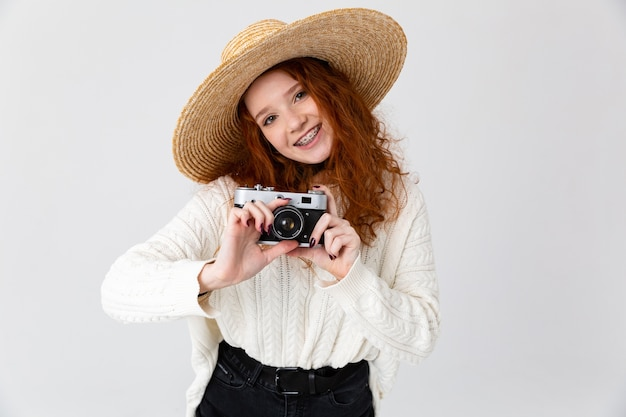 Close up portrait of a cheerful young teenage girl wearing summer hat standing isolated over white background, holding photo camera