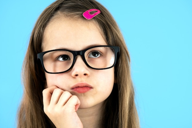 Close up portrait of a child school girl wearing looking glasses