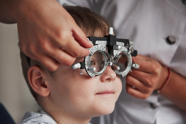 Close up portrait of child in special glasses in ophthalmologist cabinet.