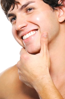 Close-up portrait of cleanshaven male face with a toothy smile