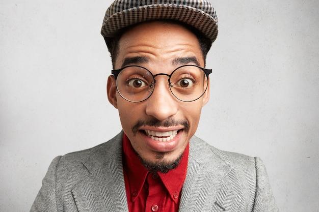 Close up ritratto di maldestro maschio comico indossa grandi occhiali, berretto e giacca, sorride con sorpresa,