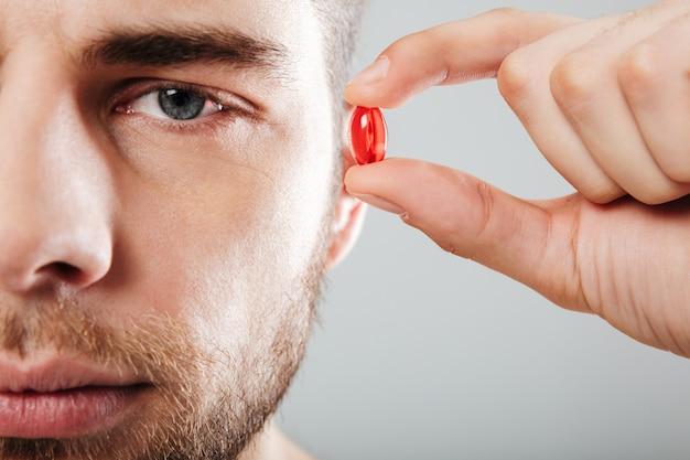 Chiuda sul ritratto di un uomo concentrato che tiene la capsula rossa