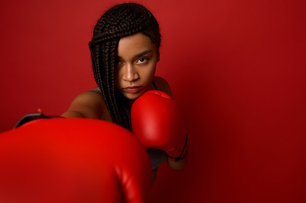 Close-up portrait of concentrated young african sports woman boxer wearing red boxing gloves, making direct hit, isolated over red background with copy space. black woman boxer punching towards camera