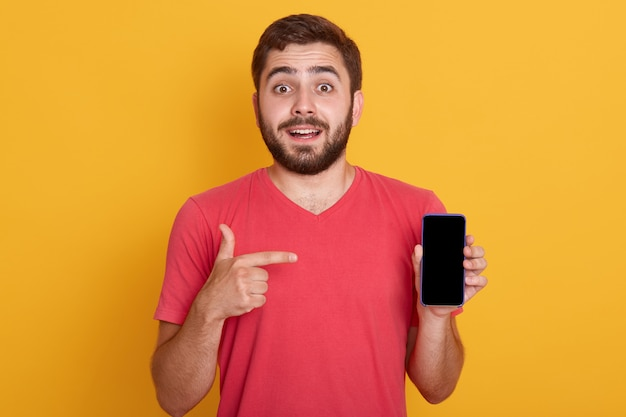 Close up portrait of confident handsome young man showing his phone and pointing with index finger on device's screen