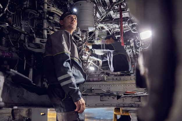 Close up portrait of confident man in uniform working inside of transport aircraft renewal technology with the modernization programe