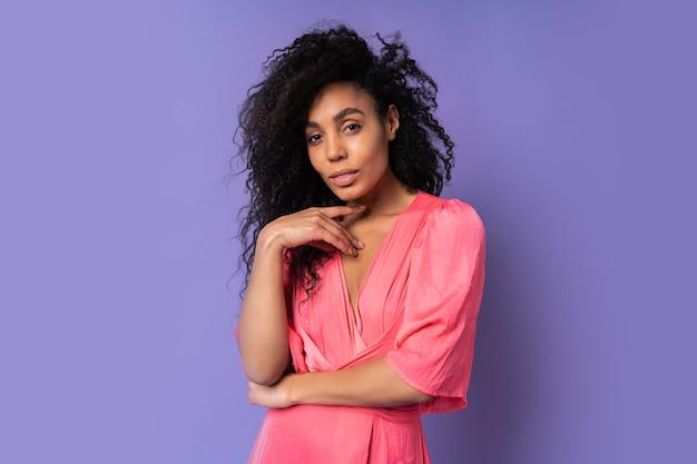 Close up ritratto di fiducioso mix gara donna con acconciatura riccia in abito rosa in piedi sopra la parete viola