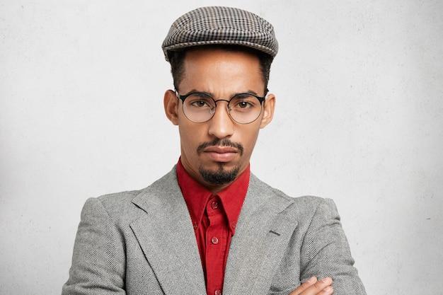 Close up ritratto di fiducioso uomo serio ha barba scura e baffi, indossa occhiali alla moda, camicia rossa e giacca, sembra seriamente