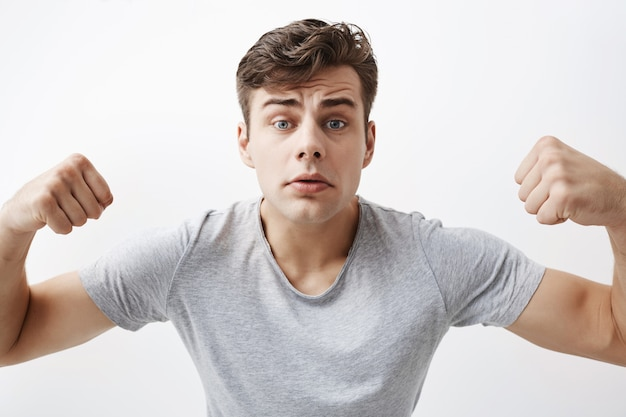 Close up portrait of confident young caucasian male athlete with muscular body, demonstrating how strong he is, boasts of himself. good-looking sportsman shows his muscles and strength.