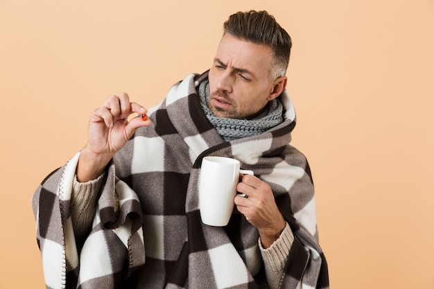 Close up portrait of a confused man wrapped in a blanket standing isolated over beige wall, showing pill capsule