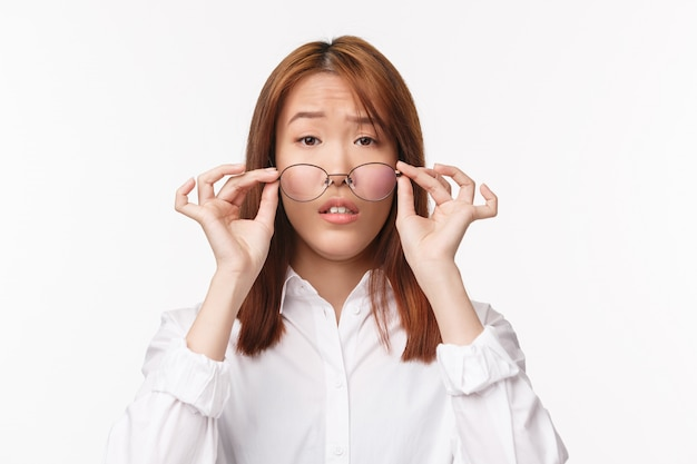 Close-up portrait of confused and uncertain cute asian girl taking-off glasses and looking uncertain, cant see in prescribed glasses with lenses that dont fit, standing  on white wall clueless