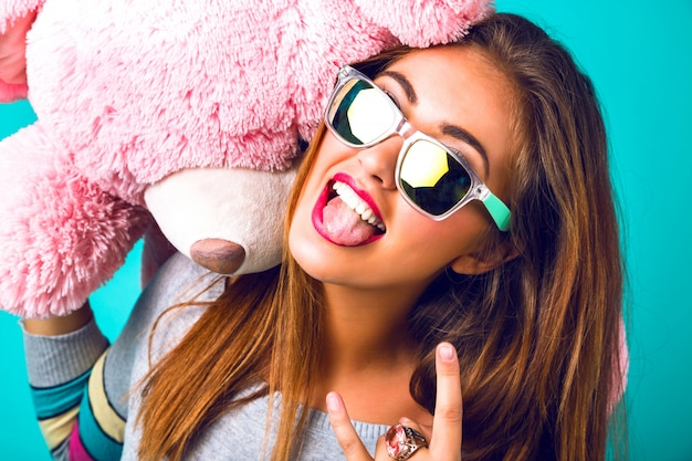 Close up portrait of crazy woman, having fun showing tongue and smiling, mirrored sunglasses, bright sweater, holding big fluffy teddy bear toy.