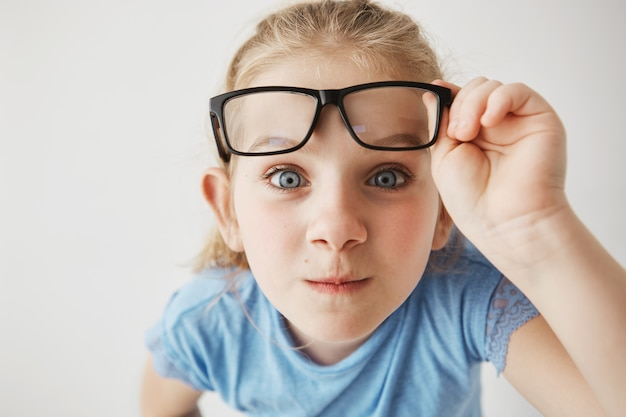 Close up portrait of curious little girl with big blue eyes standing close and , holding glasses with hand.