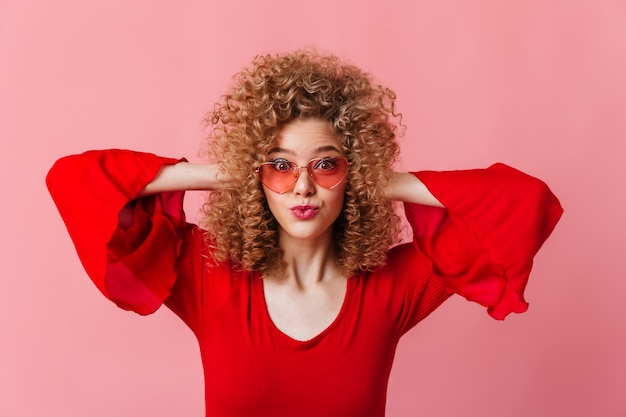 Close-up portrait of curly blonde in pink sun glasses and red top surprised on pink space.