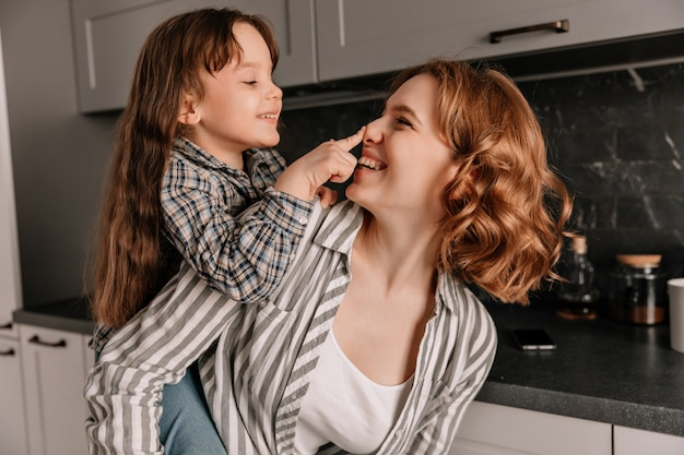 Close-up portrait of curly-haired young mom and her little cheerful daughter in kitchen.