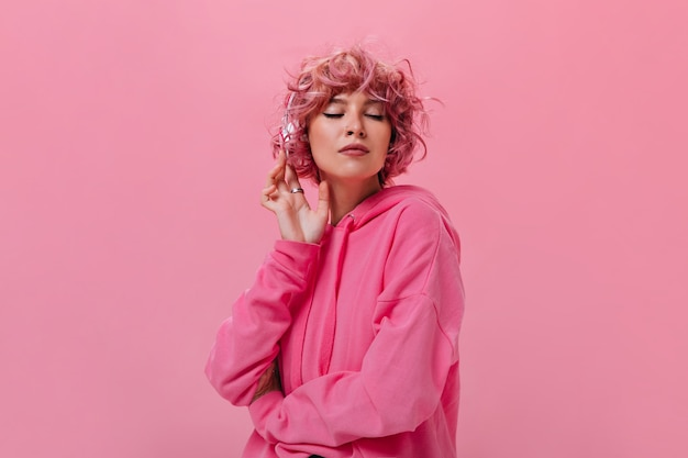 Close-up portrait of curly pink-haired woman listening to music in headphones
