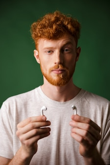 Close-up portrait of curly redhead man with raised eyebrow, showing his airpods,