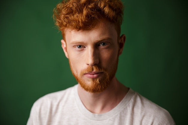 Close-up portrait of curly redhead young man with beard