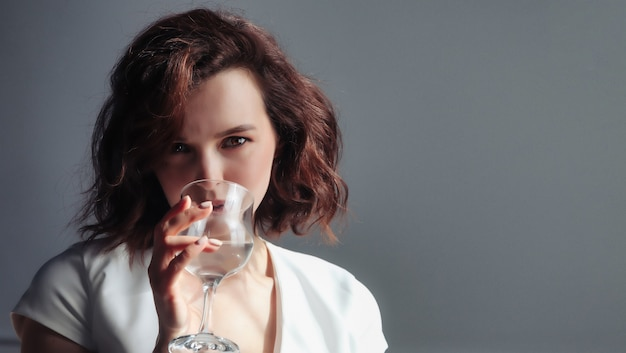 Close-up portrait of cute adult woman hold glass of water, drink and look at camera on dark background. home photo of female with fresh aqua. concept of water balance regulation and thirst quenching