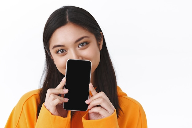 Close-up portrait of cute asian girl in orange hoodie, hiding face behind smartphone, showing mobile phone display, smiling with eyes, recommend application, app promo, white wall