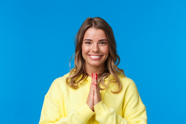 Close-up portrait of cute cheerful smiling blond girl with short hair, clasp hands together in namaste or pray gesture, thanking for help, bowing namaste gesture, standing grateful