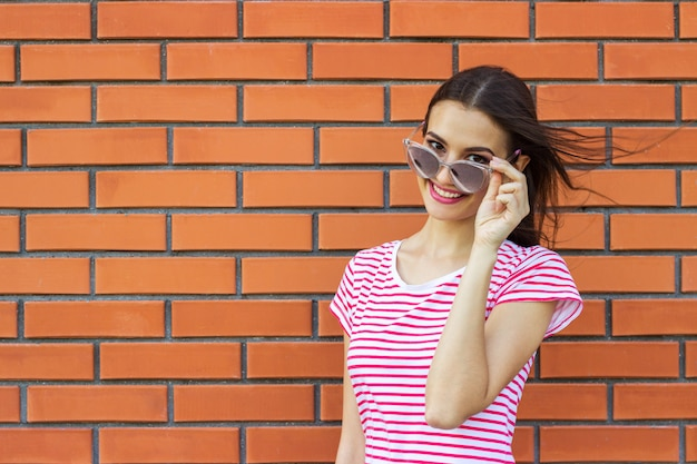 Close up portrait of cute girl wearing pink fashionable glasses looking aside over red brick wall background.