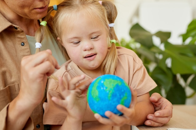 Close up portrait of cute girl with down syndrome holding planet model while studying at home with mother , copy space