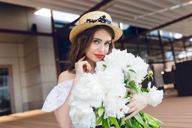 Ritratto del primo piano della ragazza carina con i capelli lunghi in cappello è seduto sul pavimento sulla terrazza. indossa un abito bianco con spalle nude, rossetto rosso. ha fiori bianchi in mano e sorride.