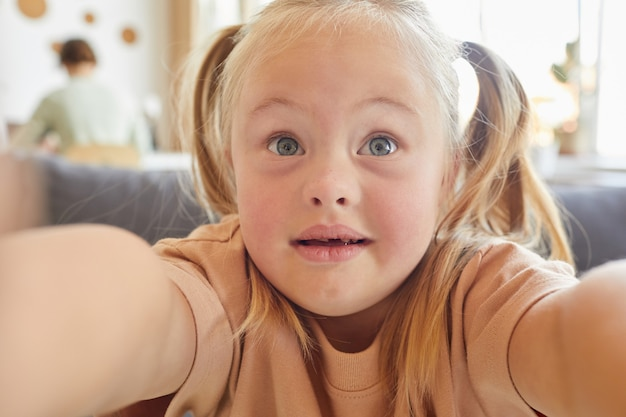 Close up portrait of cute little girl with down syndrome taking selfie and holding camera at home, copy space