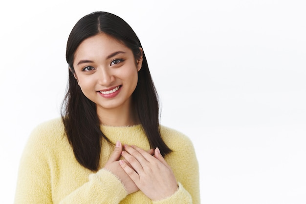 Close-up portrait cute and lovely asian girl press hands to heart, looking thankful and pleased, smiling as receive heartwarming gift, thanking being grateful, standing white wall